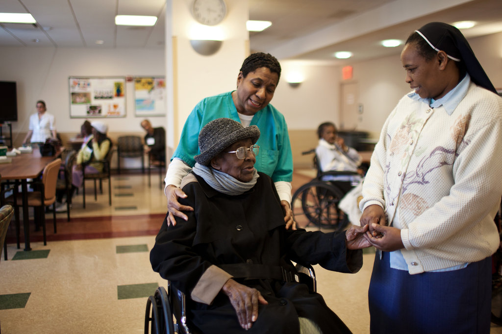 ArchCare staff help elderly woman.