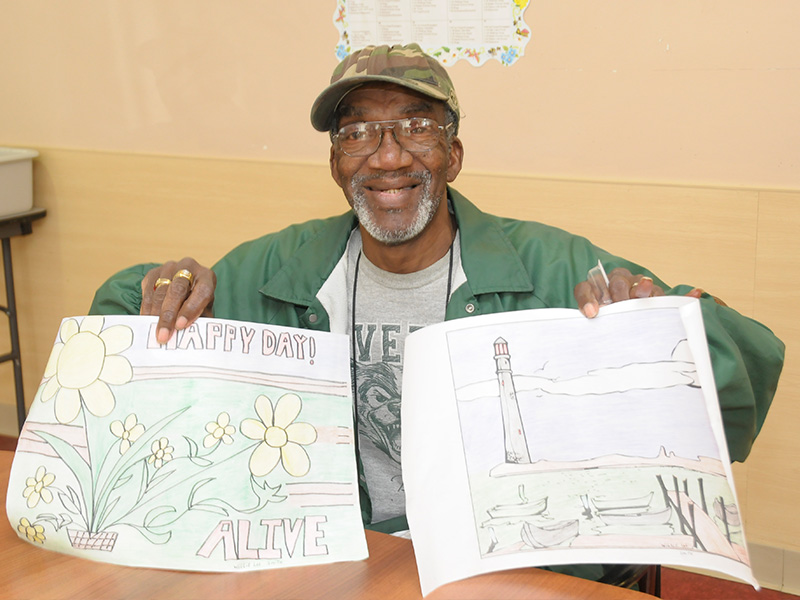 Senior social day care, man holding up two drawings