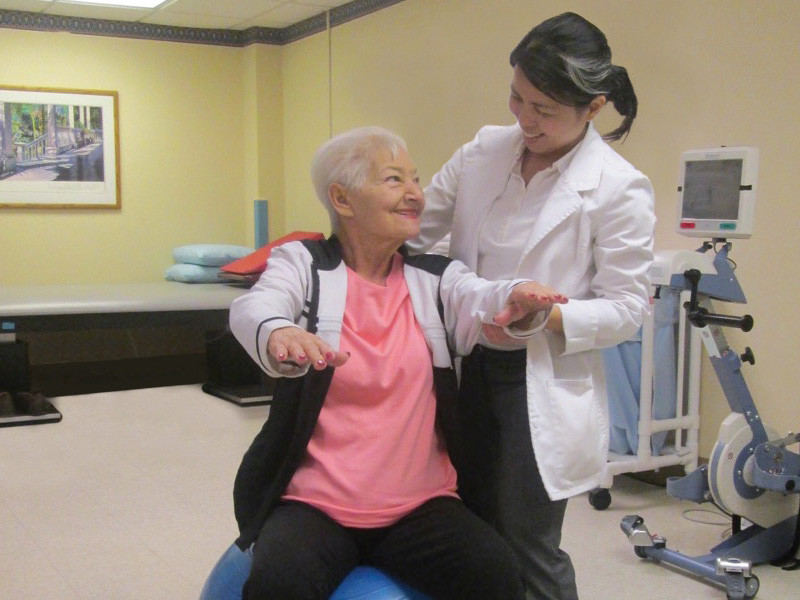 Woman helping senior exercise